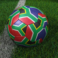 Soccer ball with south african flag d africa on green field Royalty Free Stock Photo