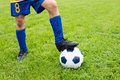 Soccer ball with their feet boy on the football field Royalty Free Stock Image