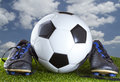 A soccer ball between two soccer shoes Stock Photography