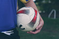 Soccer ball under player s arm a holds a his Stock Photos