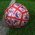 Soccer ball with united kingdom flag d uk on green field Royalty Free Stock Image