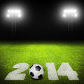 Soccer in concept with ball and date on grass field against illuminated stadium lights Stock Images