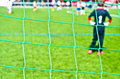 Soccer net and game close look on a with blurred players in the background Stock Photos