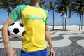 Soccer player in brasil shirt holding football copacabana rio wearing t at beach boardwalk de janeiro Royalty Free Stock Photos