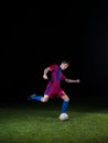 Soccer player doing kick with ball on football stadium field on black background Stock Photos
