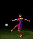 Soccer player doing kick with ball on football stadium field on black background Royalty Free Stock Images