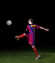 Soccer player doing kick with ball on football stadium field isolated on black background Stock Images