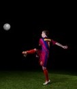 Soccer player doing kick with ball on football stadium field isolated on black background Royalty Free Stock Photography