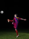 Soccer player doing kick with ball on football stadium field isolated on black background Royalty Free Stock Photo