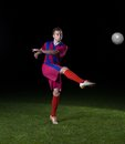 Soccer player doing kick with ball on football stadium field isolated on black background Royalty Free Stock Photos