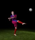 Soccer player doing kick with ball on football stadium field isolated on black background Stock Photo