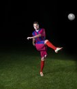 Soccer player doing kick with ball on football stadium field isolated on black background Royalty Free Stock Image