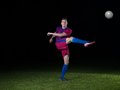 Soccer player doing kick with ball on football stadium field isolated on black background Royalty Free Stock Images