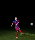 Soccer player doing kick with ball on football stadium field isolated on black background Stock Photography