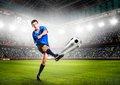 Soccer player or football is kicking ball on stadium Stock Photo