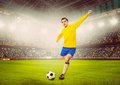 Soccer player or football is kicking ball on stadium warm colors toned Royalty Free Stock Image