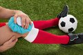 Soccer player icing knee with ice pack Royalty Free Stock Photo