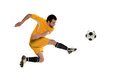 Soccer player kicking the ball isolated on a white background Stock Photo