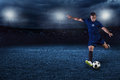 Soccer player kicking ball in a large stadium at night Royalty Free Stock Photo
