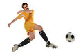 Soccer player kicking ball in mid air isolated over white background Stock Images