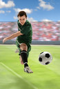 Soccer player kicking ball in stadium Stock Photography