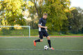 Soccer player playing with ball on football field Royalty Free Stock Photo