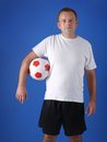 Soccer player wearing white t shirt and black shorts posing with socker ball on blue background Stock Images