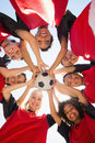 Soccer team with ball forming huddle against sky directly below shot of female clear Royalty Free Stock Image