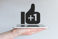 Social network thumbs up icon with plus sign concept of mobile computing and social media hand holding tablet or smart phone Royalty Free Stock Image