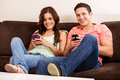 Social networking at home happy couple updating their network statuses on their cell phone while relaxing in the living room Royalty Free Stock Photos