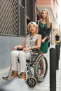 Social worker and disabled woman at stroll friendly young women on chair focus on Royalty Free Stock Images