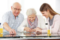 Social worker solving jigsaw puzzle a young with senior couple at home Royalty Free Stock Images
