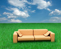Sofa on grass and cloudy sky Stock Image