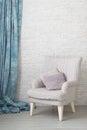 Soft armchair near brick wall.