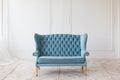 Soft blue sofa near white wall.