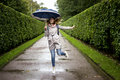Soft and blur conception. Young beautiful girl jumping with blue umbrella closeup near the green alleys from the bushes Royalty Free Stock Photo