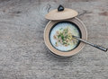 Soft-boiled rice in clay bowl with lid on a wooden tablle Royalty Free Stock Photo