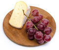 Soft cheese with grapes on a wooden board isolated white Royalty Free Stock Photo