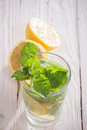 Soft drink with lemon ice and mint in a glass on a wooden table Stock Images