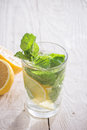 Soft drink with lemon ice and mint on a wooden table Royalty Free Stock Image