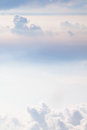 Soft pastel sky clouds and colors fill the image has a vertical orientation and was photographed from an airplane at feet Stock Photos