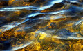 Soft rippling waters in shades of gold with light reflecting on surface Stock Image