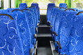Soft seats for passengers inside saloon of empty city bus with grey floor Stock Photo