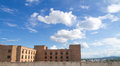 Soft white clouds against blue sky and brick building Royalty Free Stock Photo