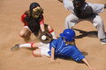 Softball player sliding into home plate while umpire rules safe Royalty Free Stock Photography