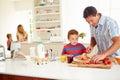 Sohn helfendes vater to prepare family frühstück in der küche Stockfotografie