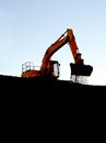Soil falling from dozer bucket large orange bulldozer on ridge line dropping Stock Image
