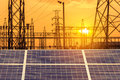 Solar cells in power station with  high voltage electric pylon pillars substation on sunset. Royalty Free Stock Photo