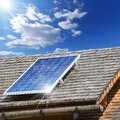 Solar panel on a old roof with wooden shingles and with reflection of blue sky Stock Photos