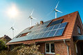 Solar panel on a roof of a house and wind turbins arround Royalty Free Stock Photo